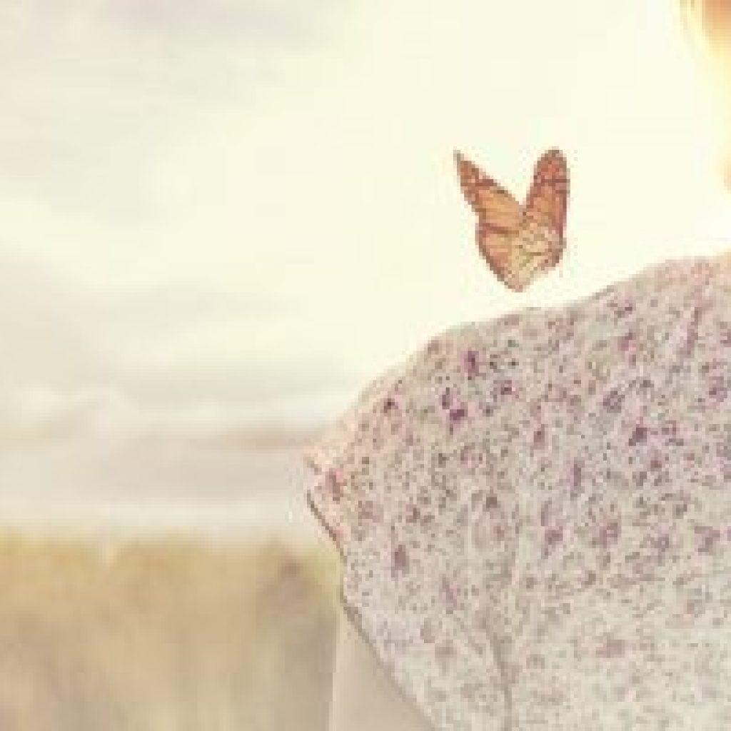 Bild med fjäril som sitter på en kvinnas axel